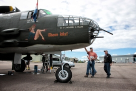 Bob Moore, right, shows visitors the B-25J Mitchell bomber on the afternoon of Aug. 3 at the Glacier Jet Center. - Justin Franz | Flathead Beacon
