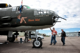Bob Moore, right, shows visitors the B-25J Mitchell bomber on the afternoon of Aug. 3 at the Glacier Jet Center. - Justin Franz   Flathead Beacon
