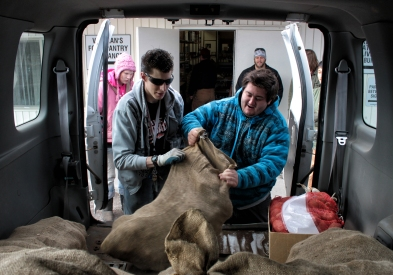 Chad Scheschy, left, helps Donovan Leskovec unload a bag of potatos at the Northwest Montana Veteran's Food Pantry in Evergreen on Nov. 14. - Justin Franz   Flathead Beacon.