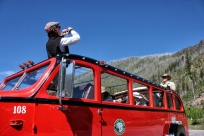 Sherri Camperchioli takes a passenger's photo at the intersection of the Camas and North Fork roads. Of the 35 Red Buses built for Glacier National Park, 33 operate today. One was preserved in its original condition by the National Park Service and another, No. 100, was lost in an accident. Justin Franz | Flathead Beacon.