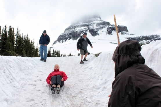 Pauline Morey, center, slides down a snowfield at Logan Pass on the first day all 50 miles of the Going-to-the-Sun Road were open. Morey was traveling from Ireland with a group of friends. Justin Franz | Flathead Beacon.