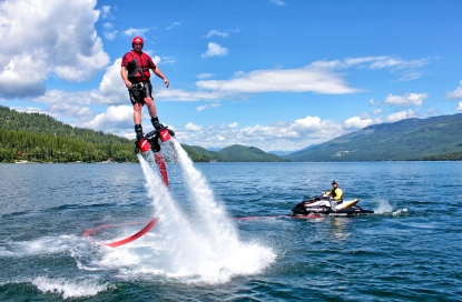 Shawn Finley, left, rides a flyboard on Whitefish Lake. The board is propelled with water from a Jet Ski. Justin Franz | Flathead Beacon.