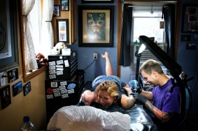 Jake Bertelsen works on a tattoo on Andrea Briggs on June 25, 2015. Justin Franz | Flathead Beacon