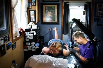 Jake Bertelsen works on a tattoo on Andrea Briggs on June 25, 2015. Justin Franz | Flathead Beacon