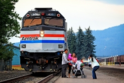 """Jayme Miller takes a photo of John and Kerry Loewen in front of the Amtrak Exhibit Train that was on display in Whitefish on Aug. 15 and 16. The five-car train is led by an histoic diesel locomotive and features aritacts from Amtrak's 44-year history. The train travels the country and makes stops like this one about two dozen times a year. Amtrak spokesperson Rob Eaton said the railroad wanted to bring the train to Whitefish this summer to thank the community for supporting the Empire Builder. """"We want to reinforce our commitment to this community,"""" he said. Justin Franz 