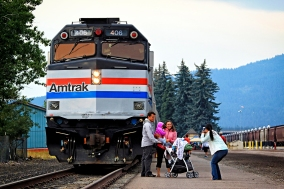 """Jayme Miller takes a photo of John and Kerry Loewen in front of the Amtrak Exhibit Train that was on display in Whitefish on Aug. 15 and 16. The five-car train is led by an histoic diesel locomotive and features aritacts from Amtrak's 44-year history. The train travels the country and makes stops like this one about two dozen times a year. Amtrak spokesperson Rob Eaton said the railroad wanted to bring the train to Whitefish this summer to thank the community for supporting the Empire Builder. """"We want to reinforce our commitment to this community,"""" he said. Justin Franz   Flathead Beacon."""